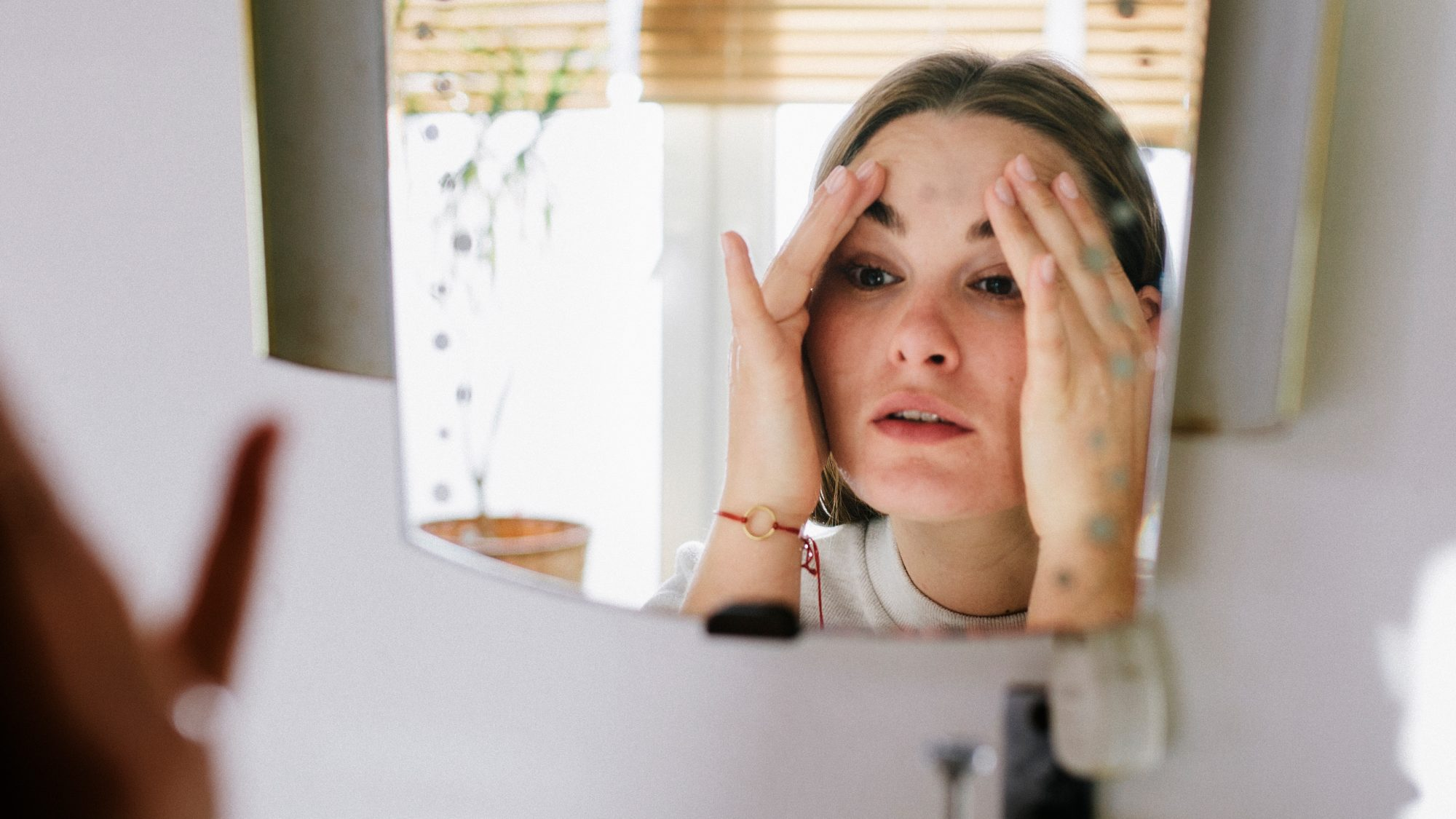 woman with facial eczema looking in mirror