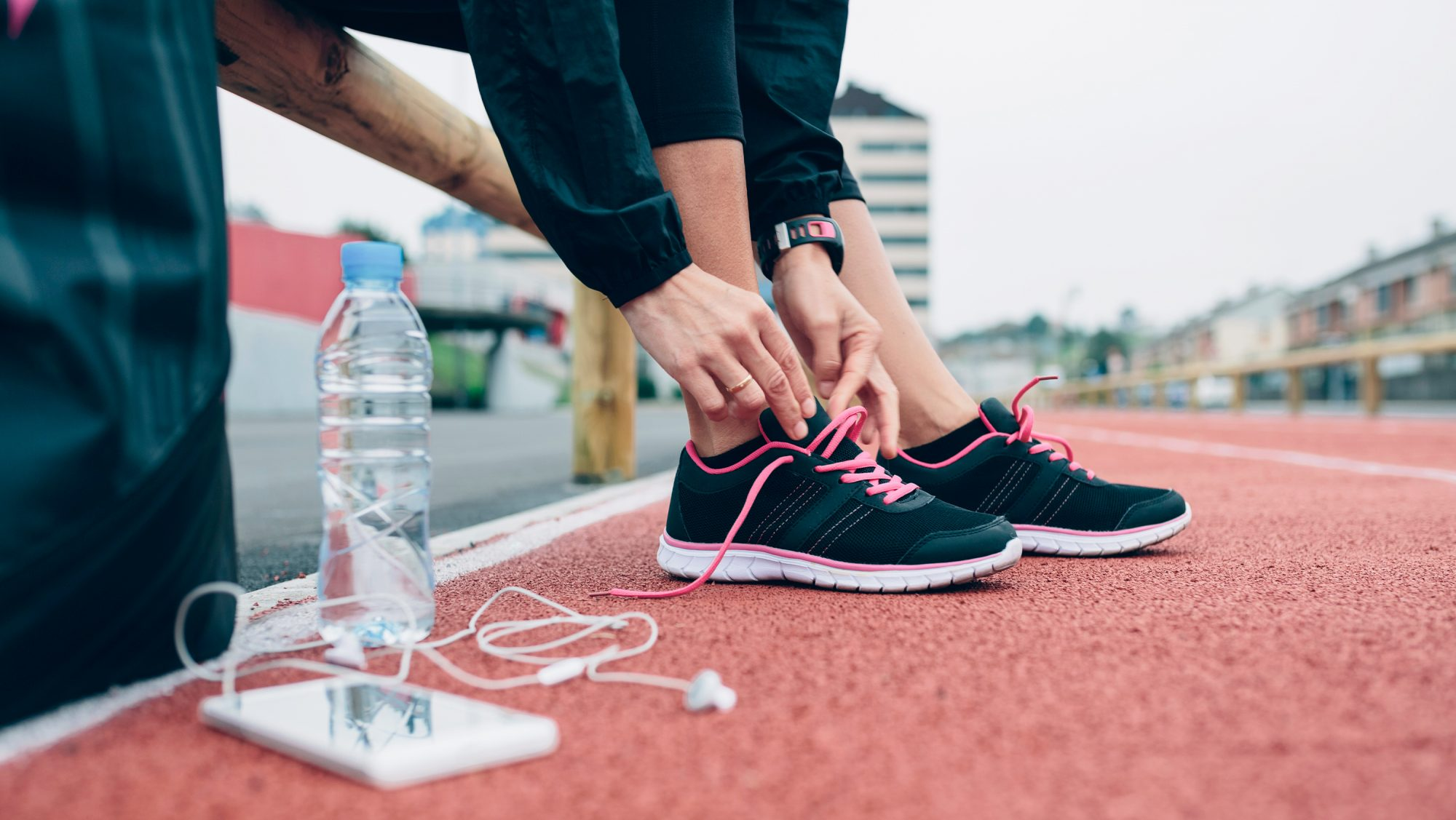 woman tying running sneakers for her afternoon workout