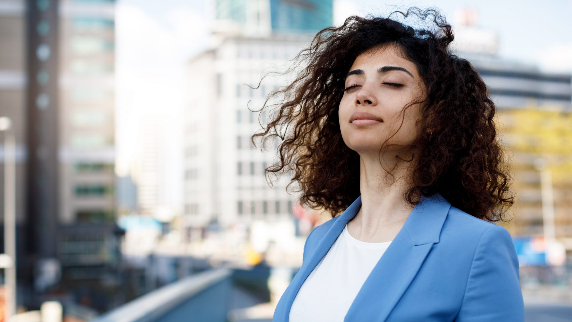 How to Meditate at Work: business woman closing her eyes outside