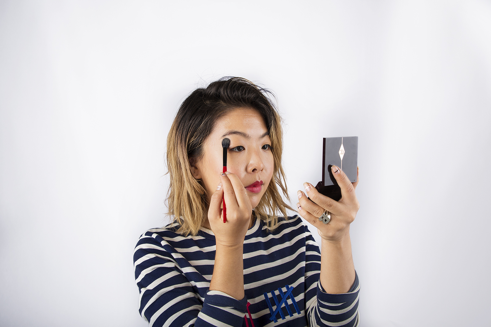 girl applying powder to face and looking in handheld mirror