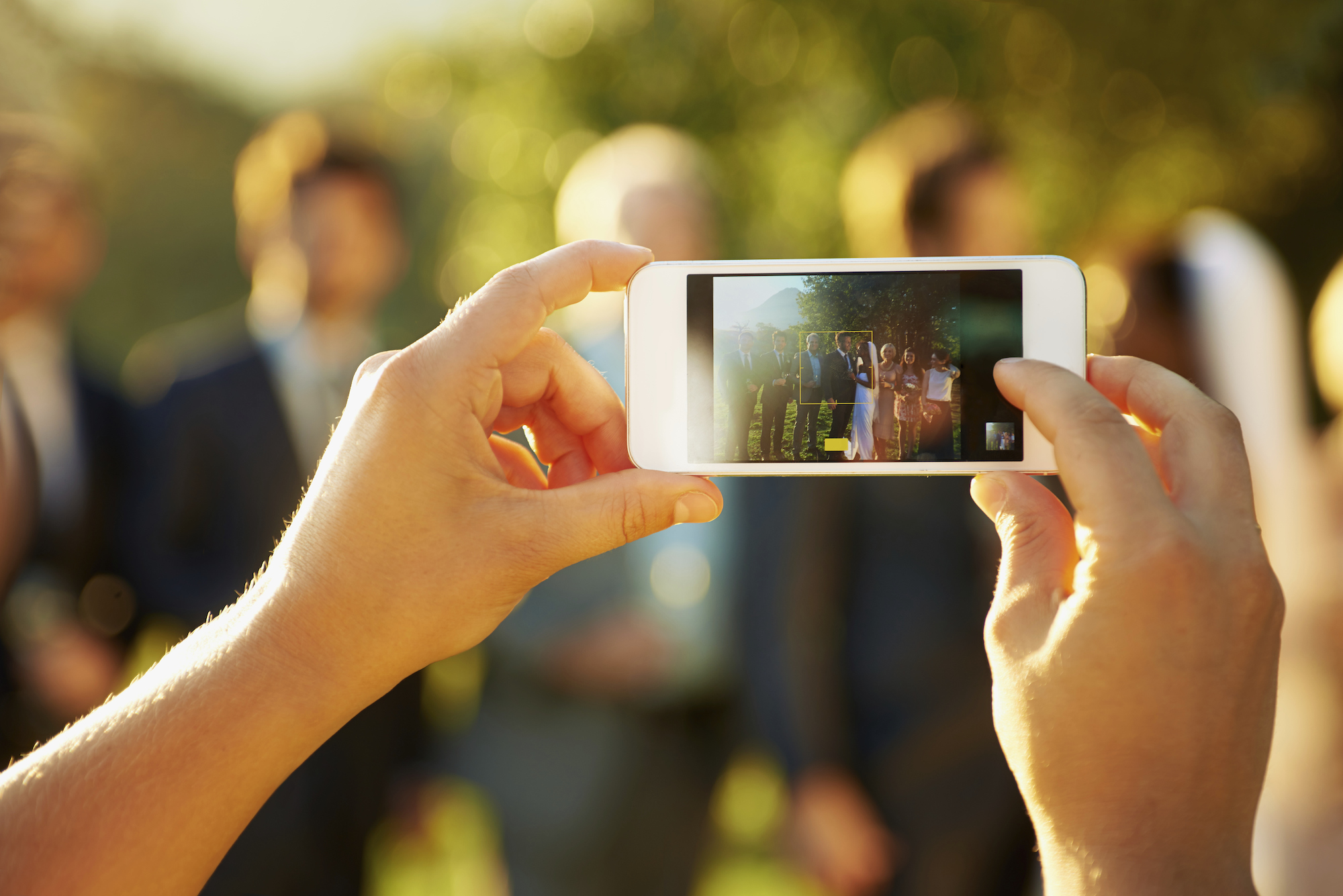 Taking a picture of the wedding party with a smartphone.