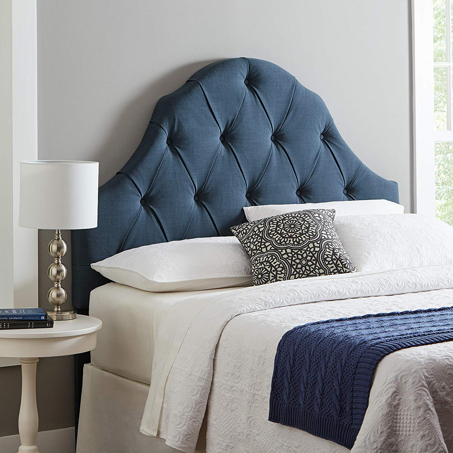 Blue tufted headboard on bed from Amazon