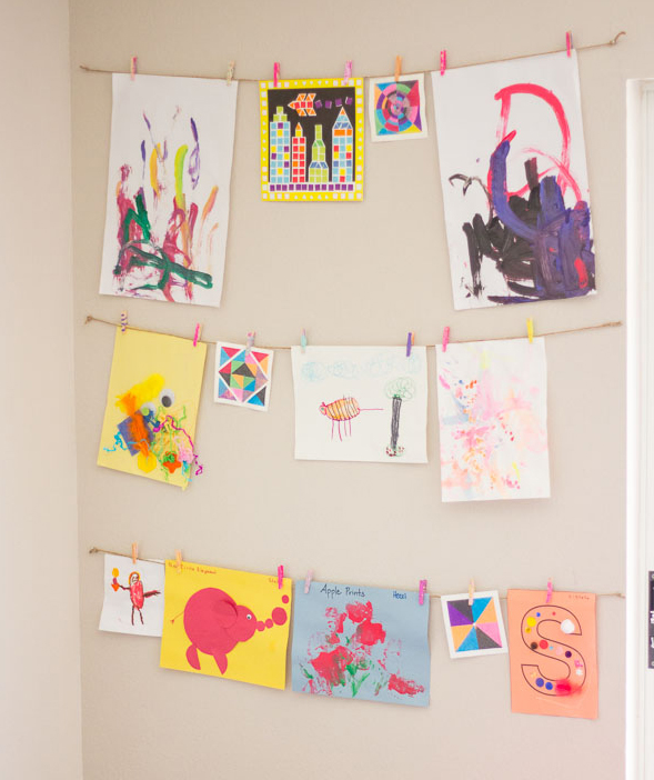 Kids' art hung with twine and clothespins