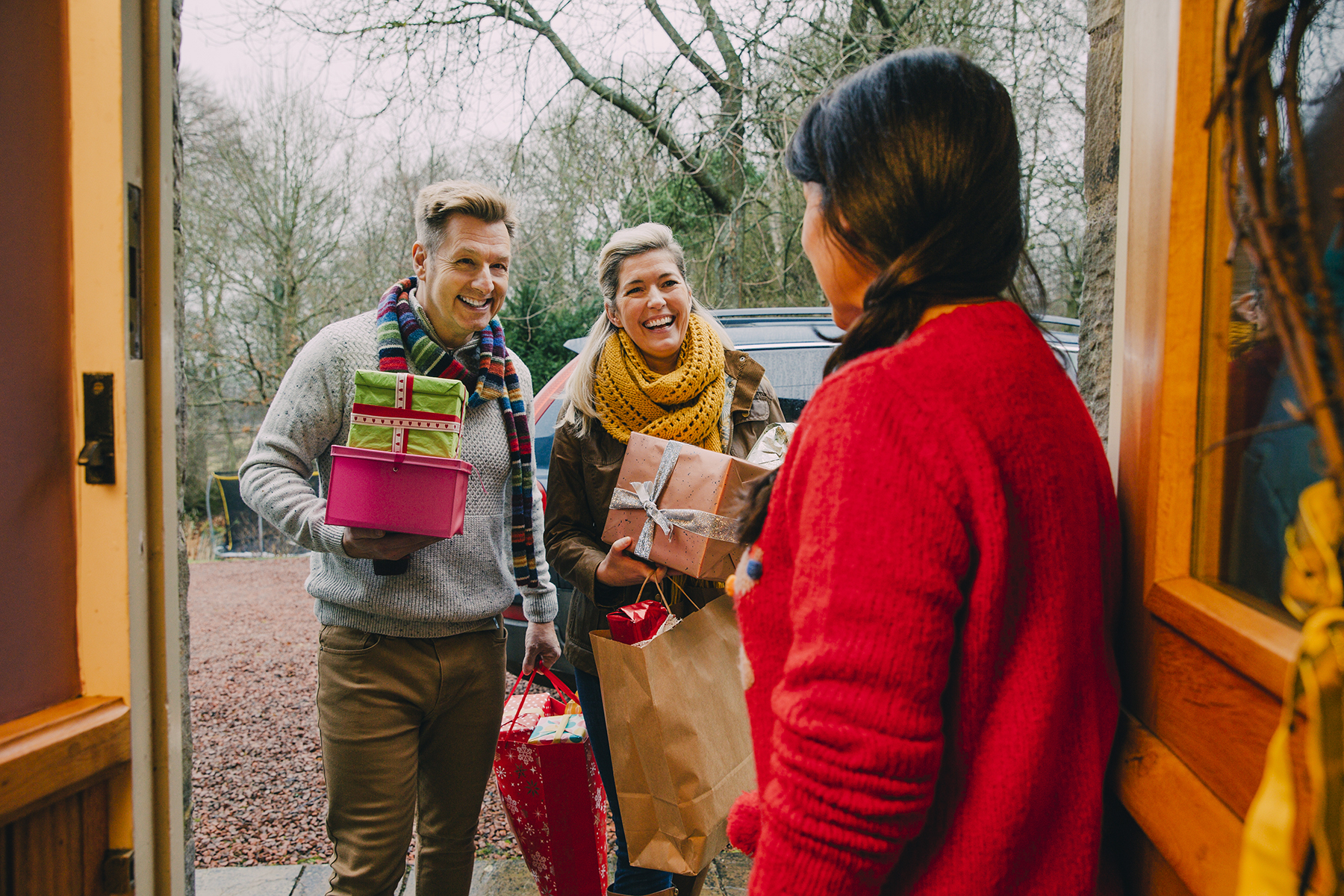 Family members arriving at house with holiday gifts