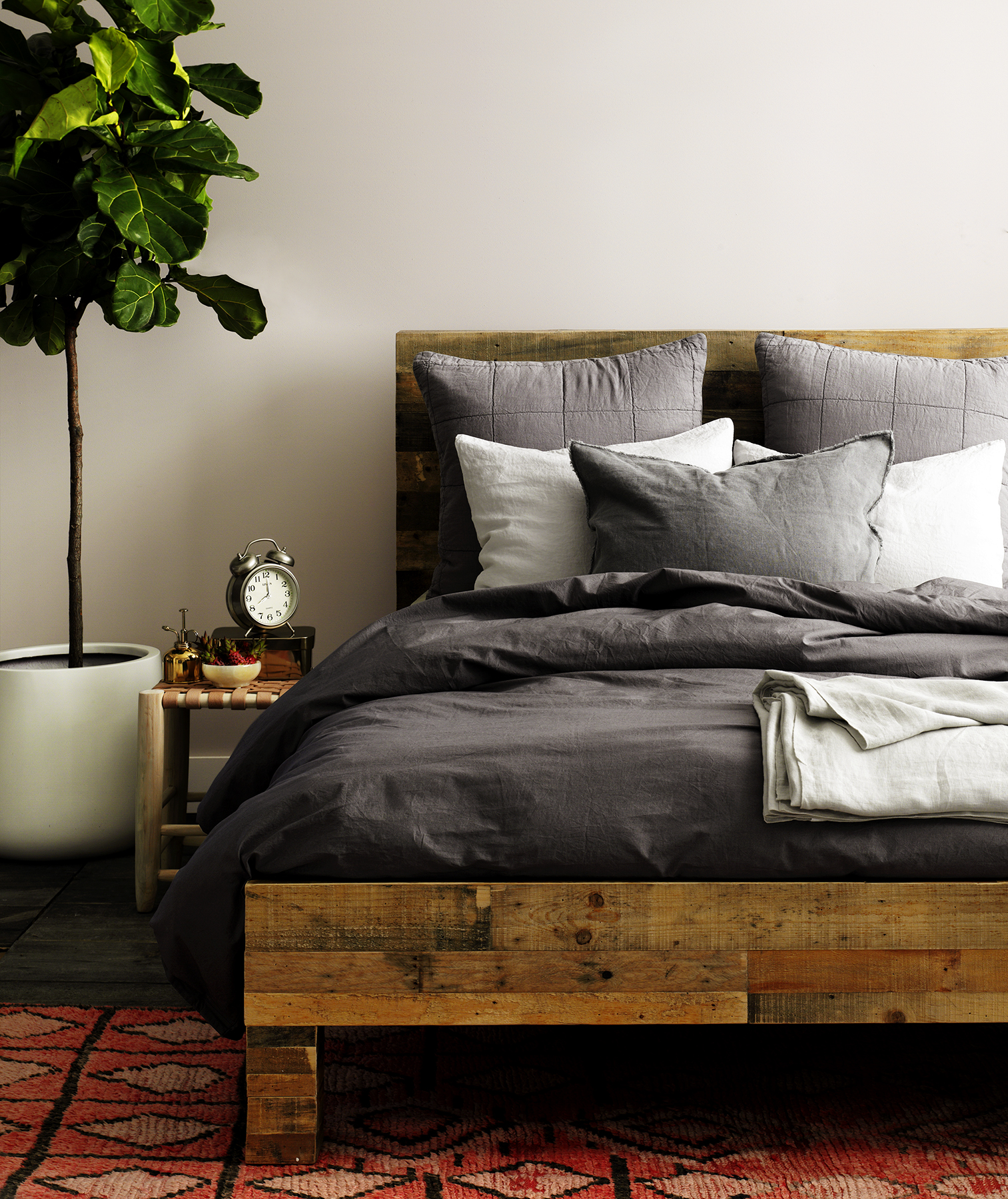 Wooden bed with linens in shades of gray