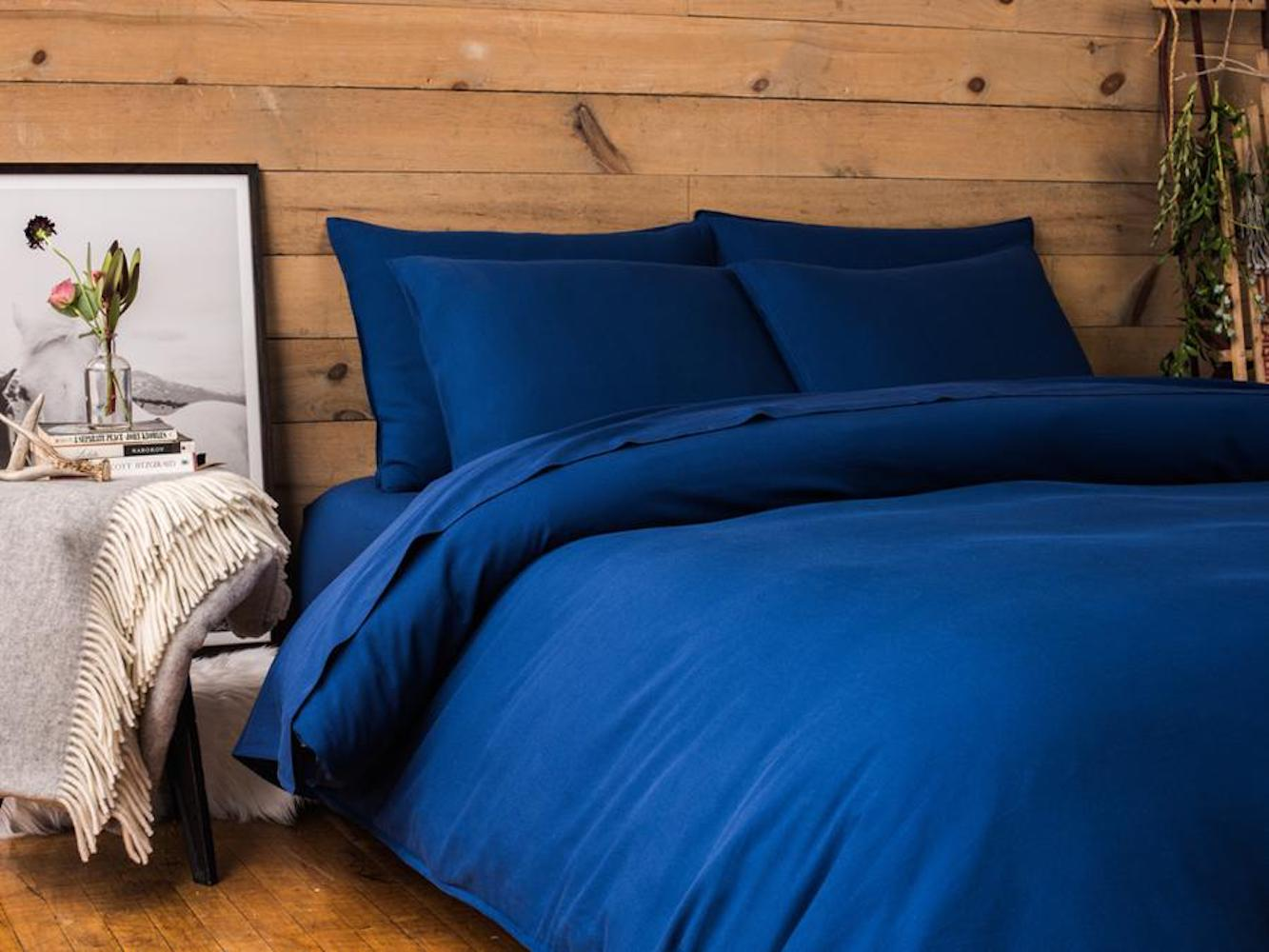 cozy bed with blue duvet and wooden headboard
