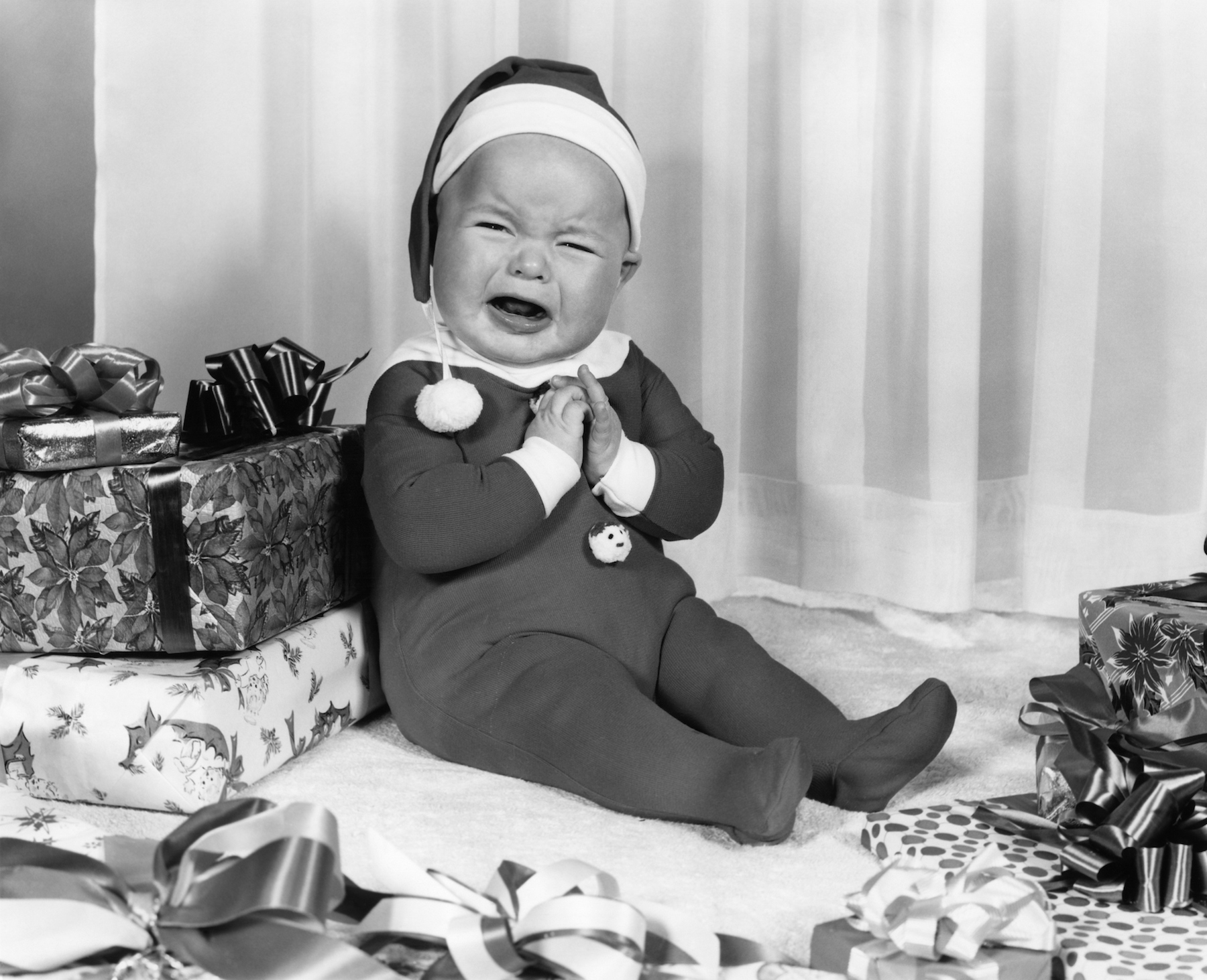 Crying baby sitting on Christmas gifts