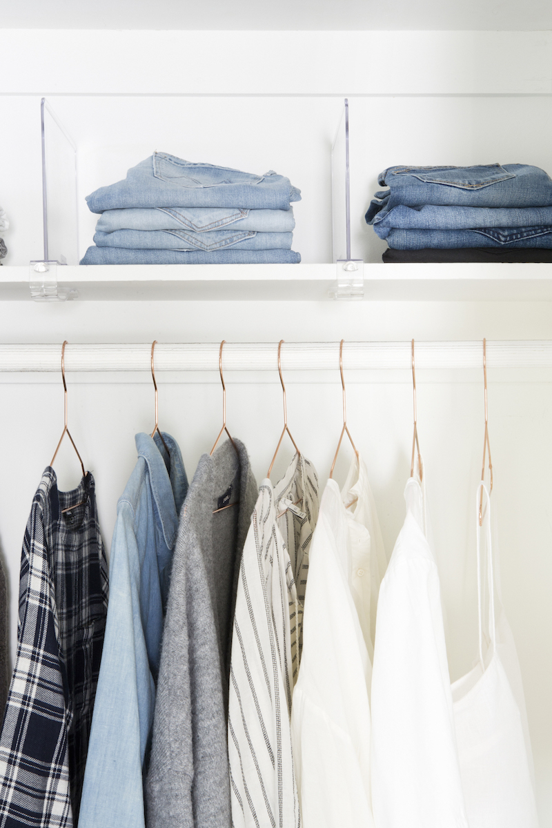 Closet organizing, copper clothing hangers and folded jeans in tidy closet