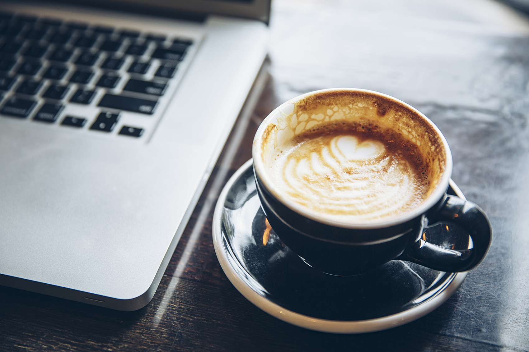 Close up of cup of coffee with heart and laptop