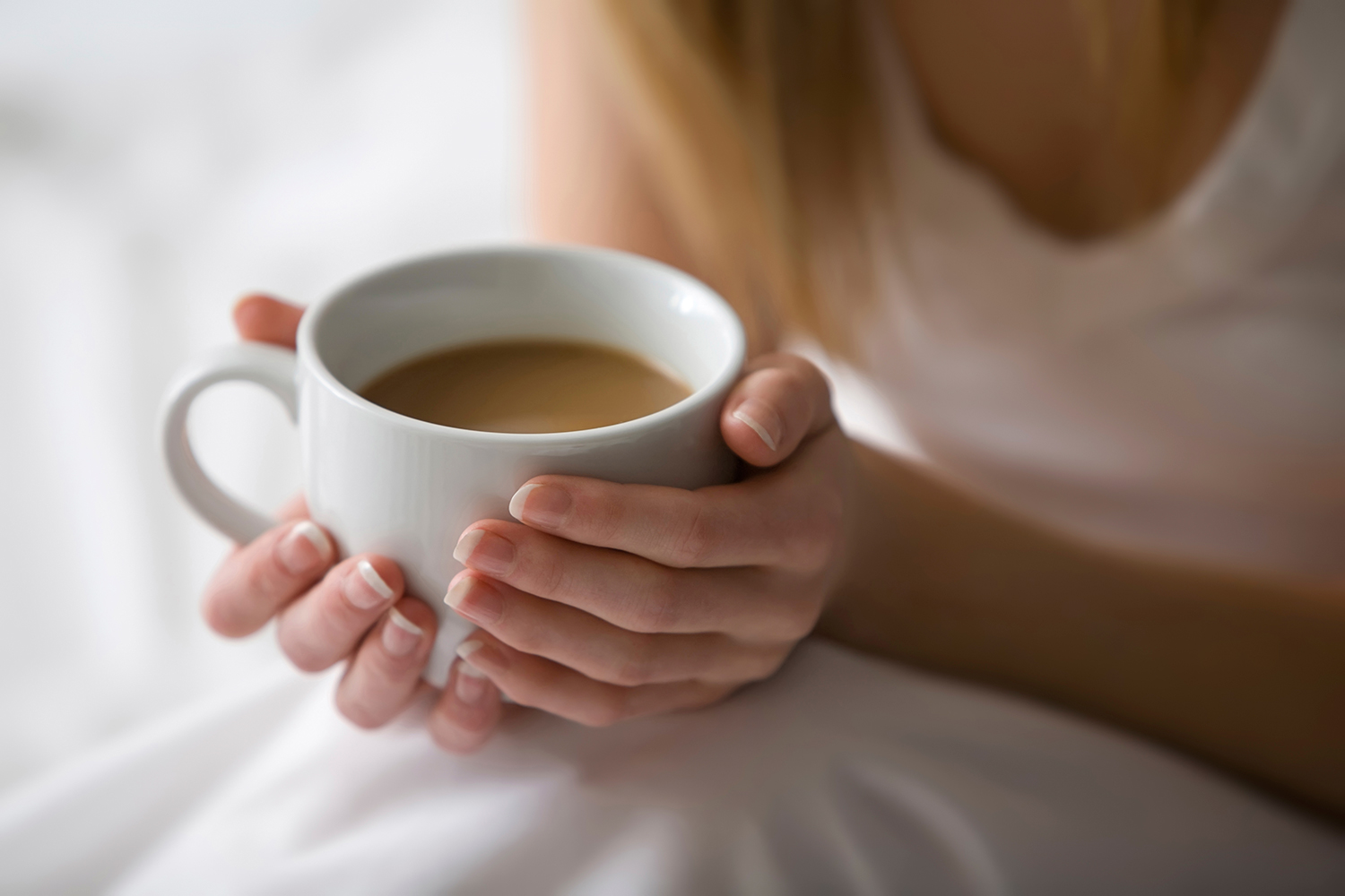 Woman Holding Coffee Cup on Bed