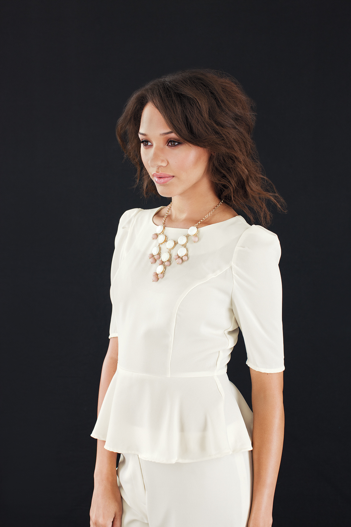 Model wearing white top and costume jewelry