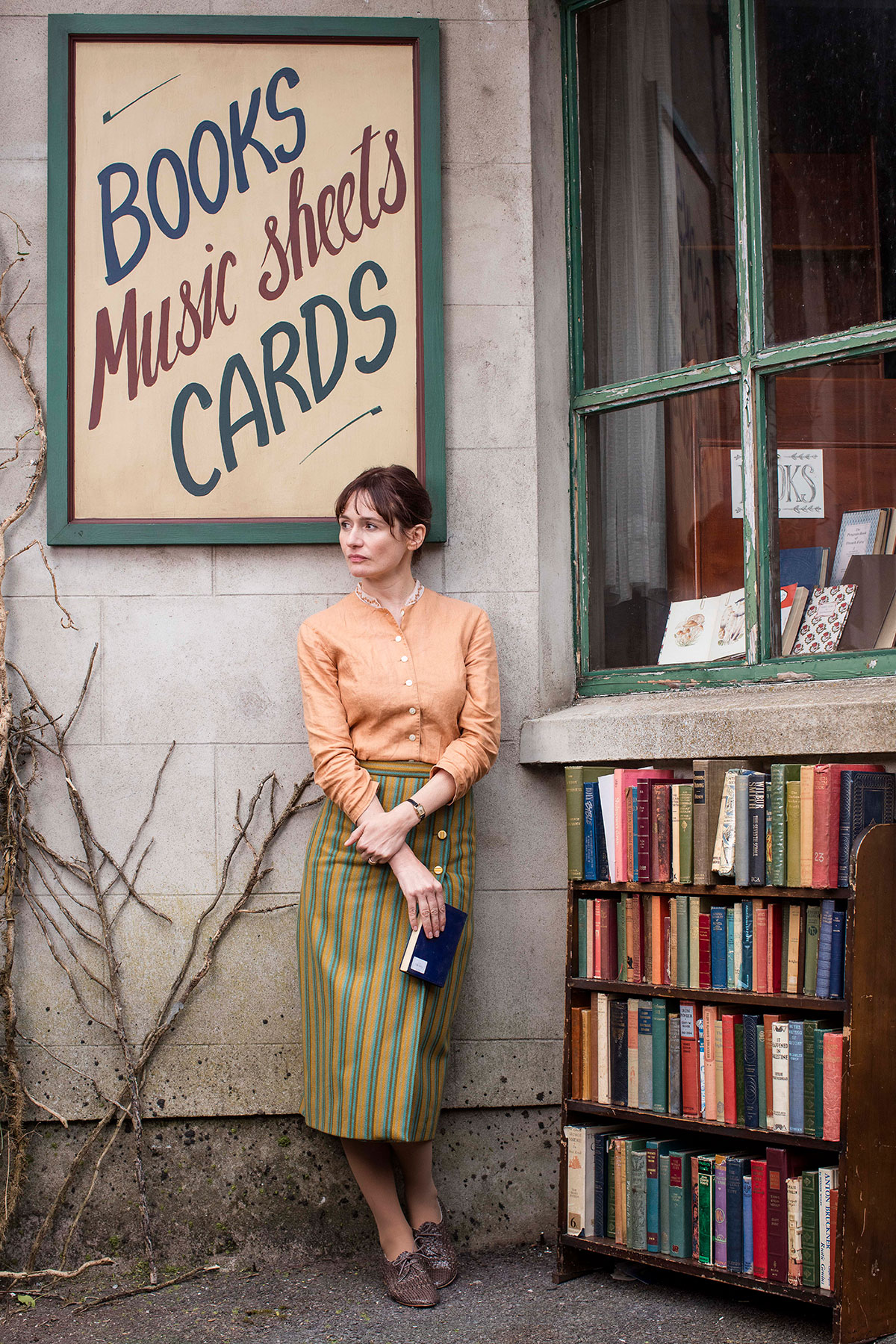 Actress Emily Mortimer stands outside her bookstore in The Bookshop movie