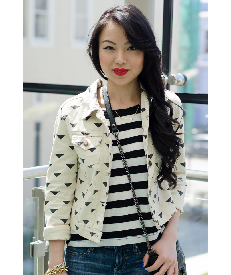 Woman wearing black and white printed denim jacket and striped shirt