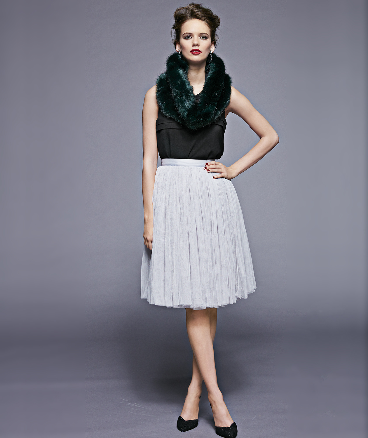Model with green faux fur stole and gray skirt
