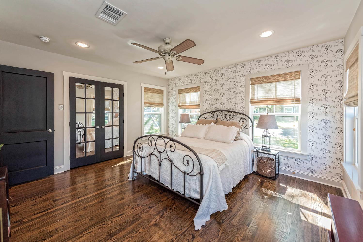 Pretty Patterned Bedroom with floral wallpaper and metal bed frame