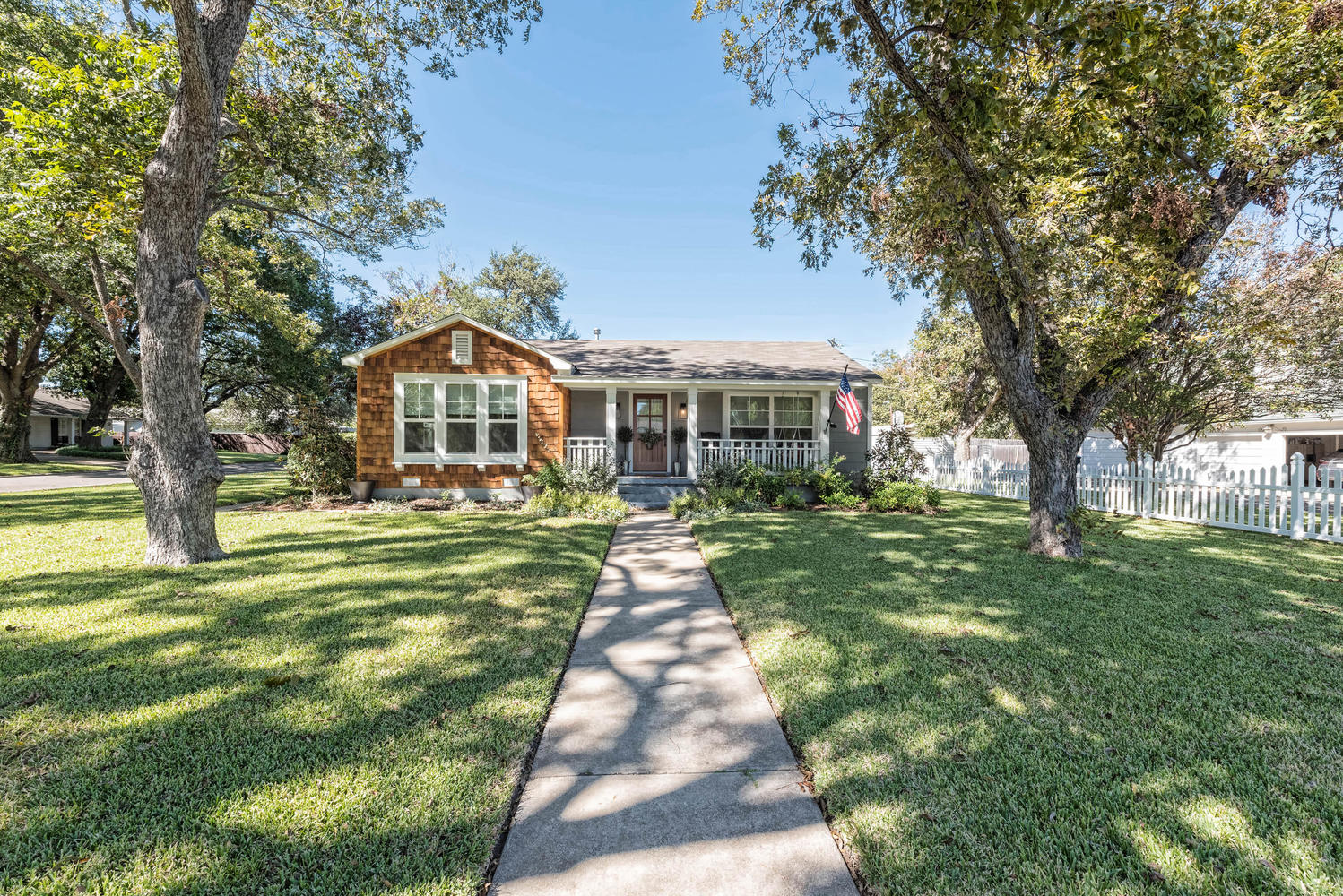 Fixer Upper home entrance with front lawn and small porch