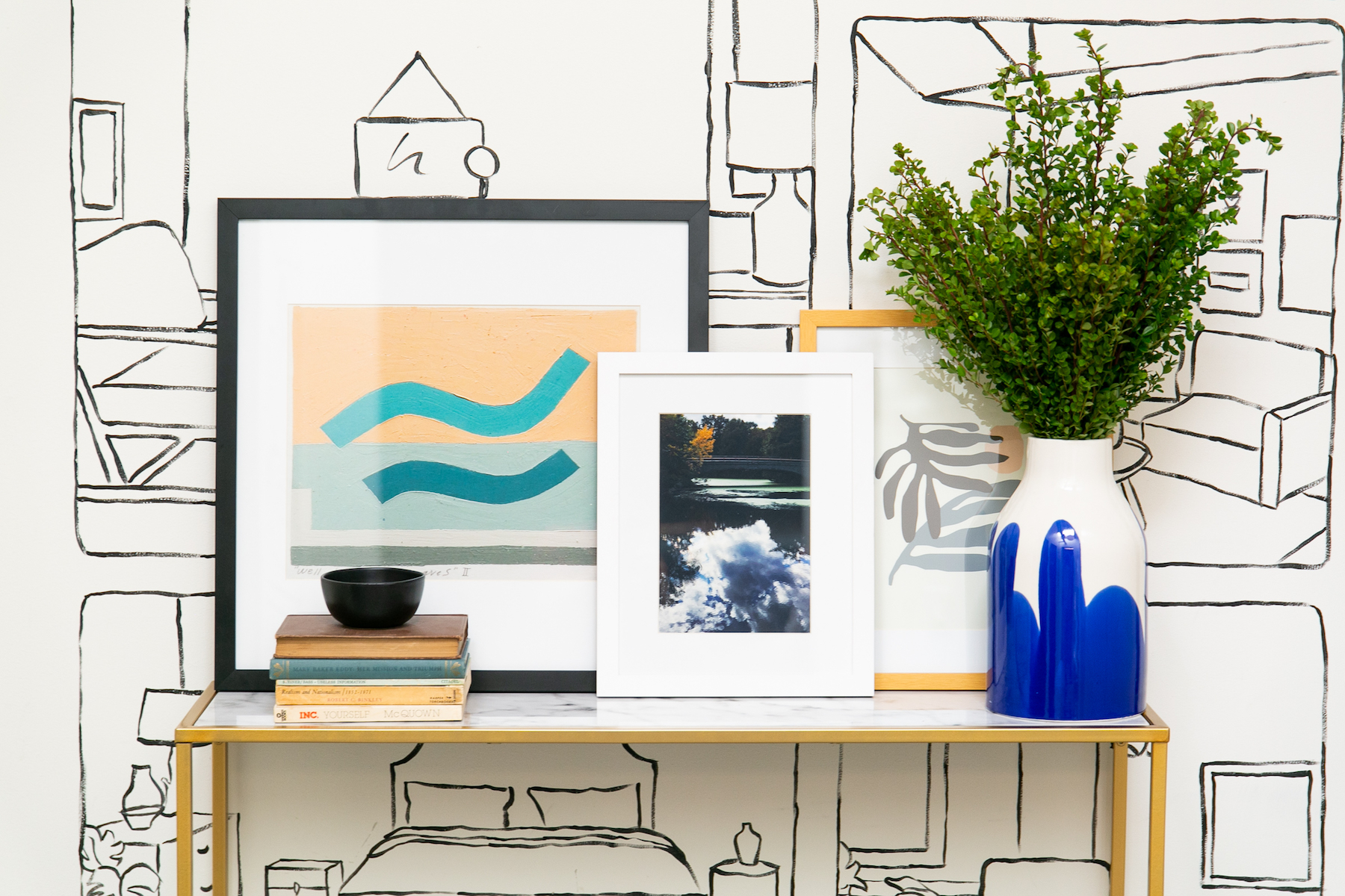 Three art pieces leaning against console table