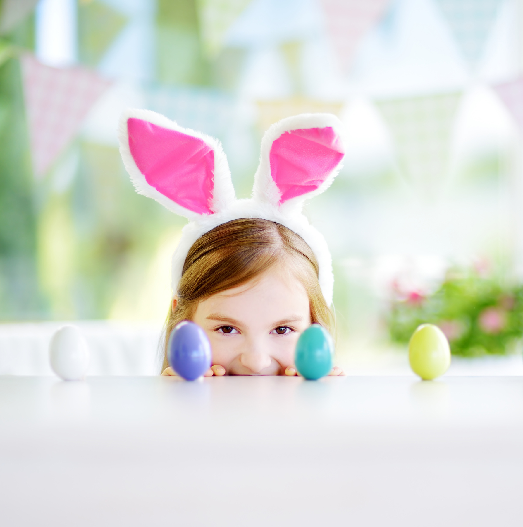 Little girl with bunny ears and Easter eggs