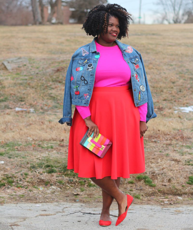 Woman wearing denim jacket with bold-colored top and skirt