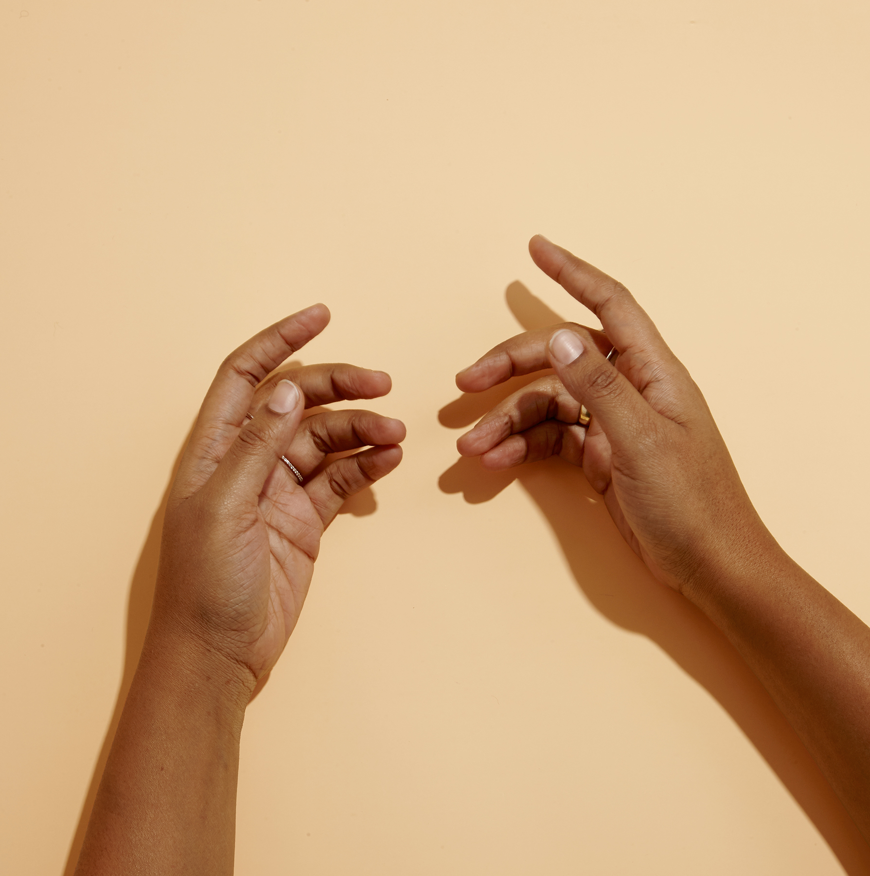Two hands on peach background
