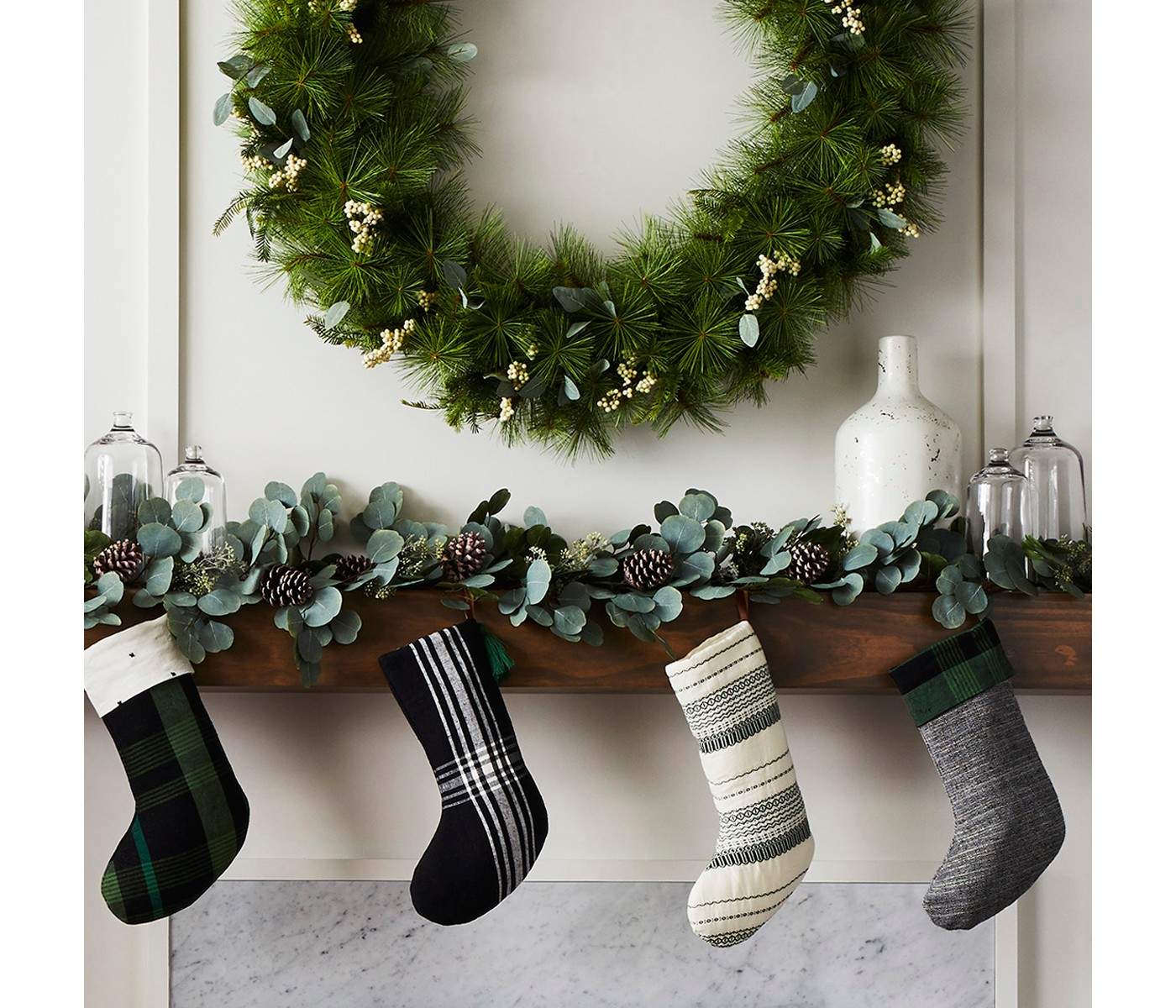 White, Black, and Green Stockings hung on mantel