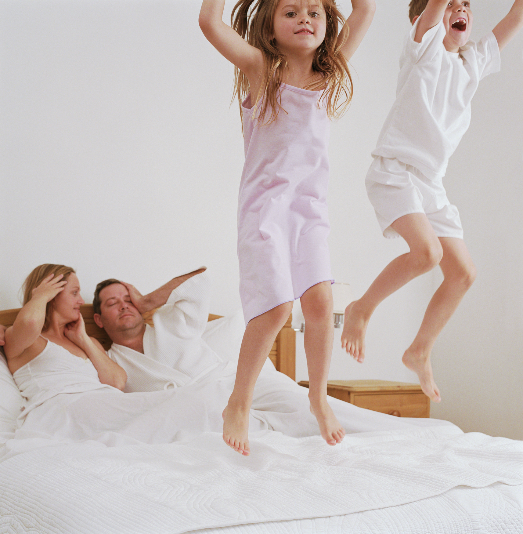 Kids jumping on parents bed