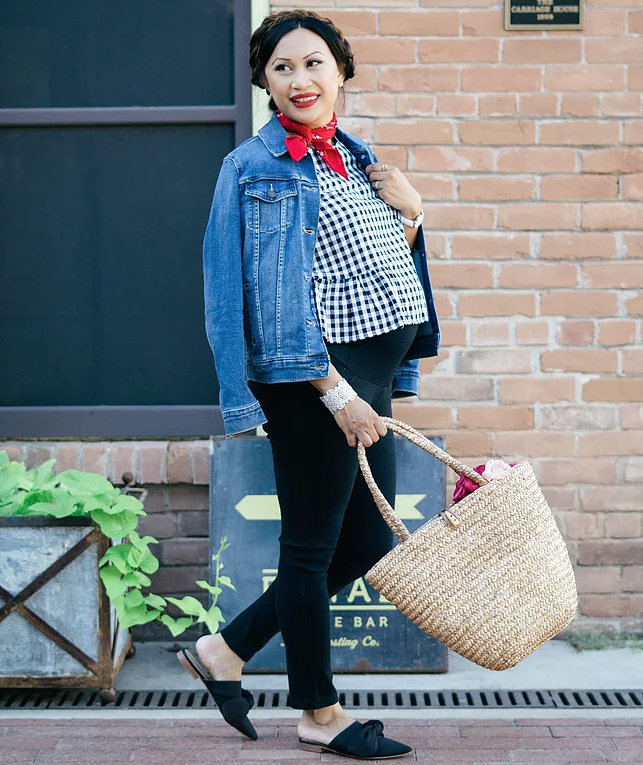 Woman wearing denim jacket with gingham top and red scarf