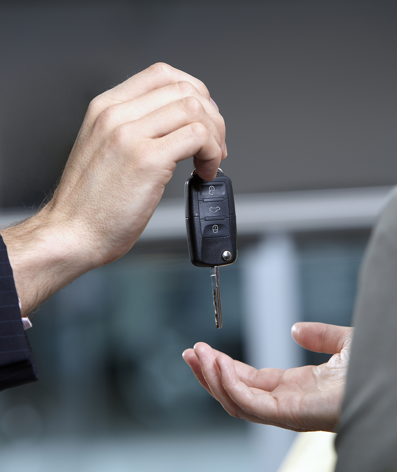 Car salesman handing over key
