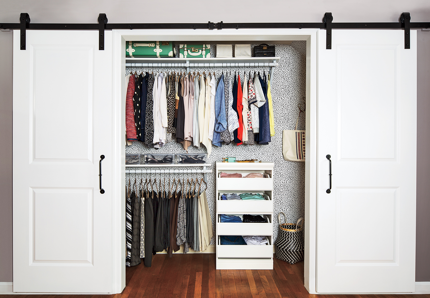 Organized closet with clothes hanging up in it