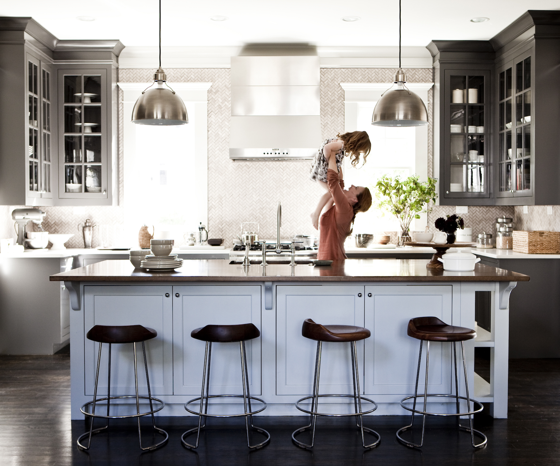 Pretty kitchen with blue cabinets, stool, mother, and daughter