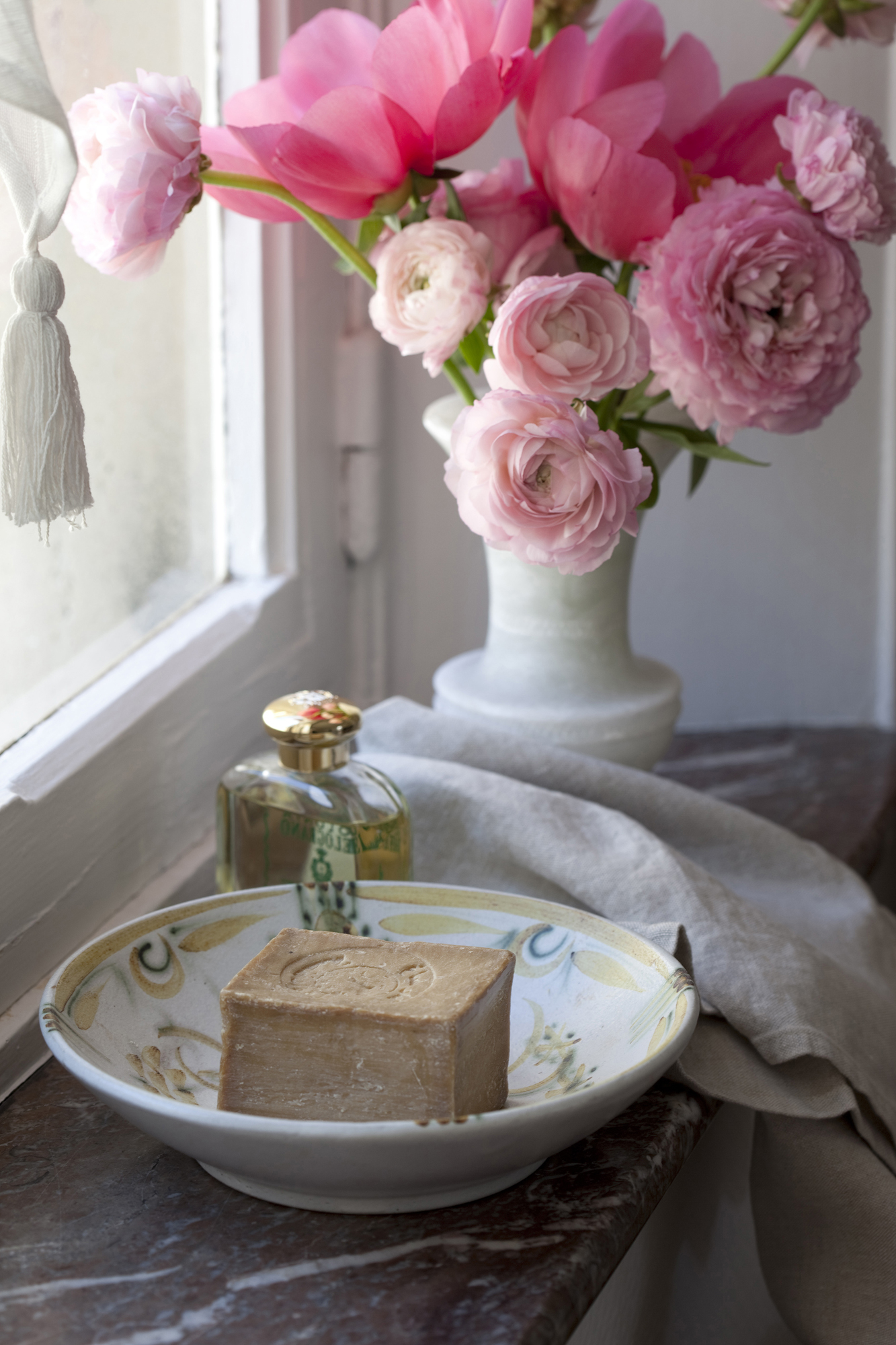 Vintage soap dish and flowers in a small bathroom