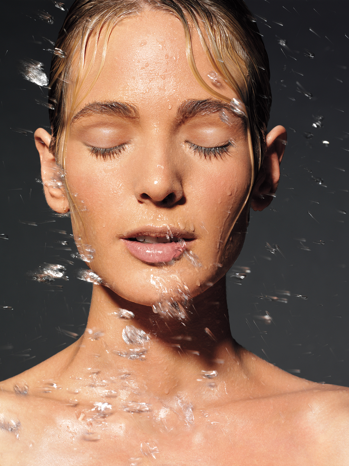 Woman with water splashing on her face