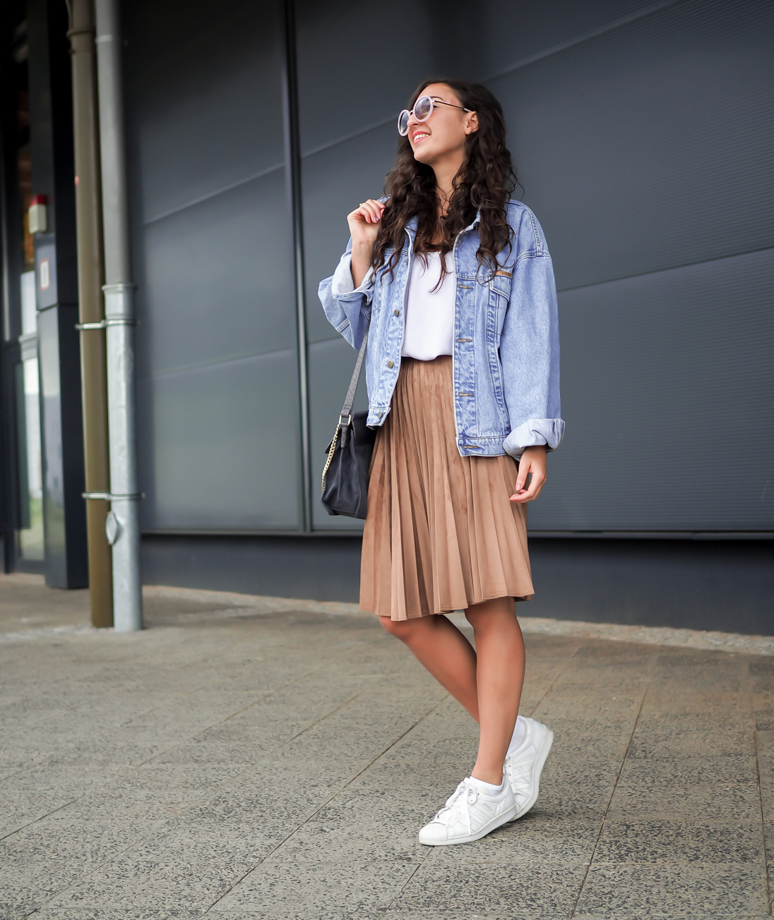 Woman wearing slouchy denim jacket with pleated skirt