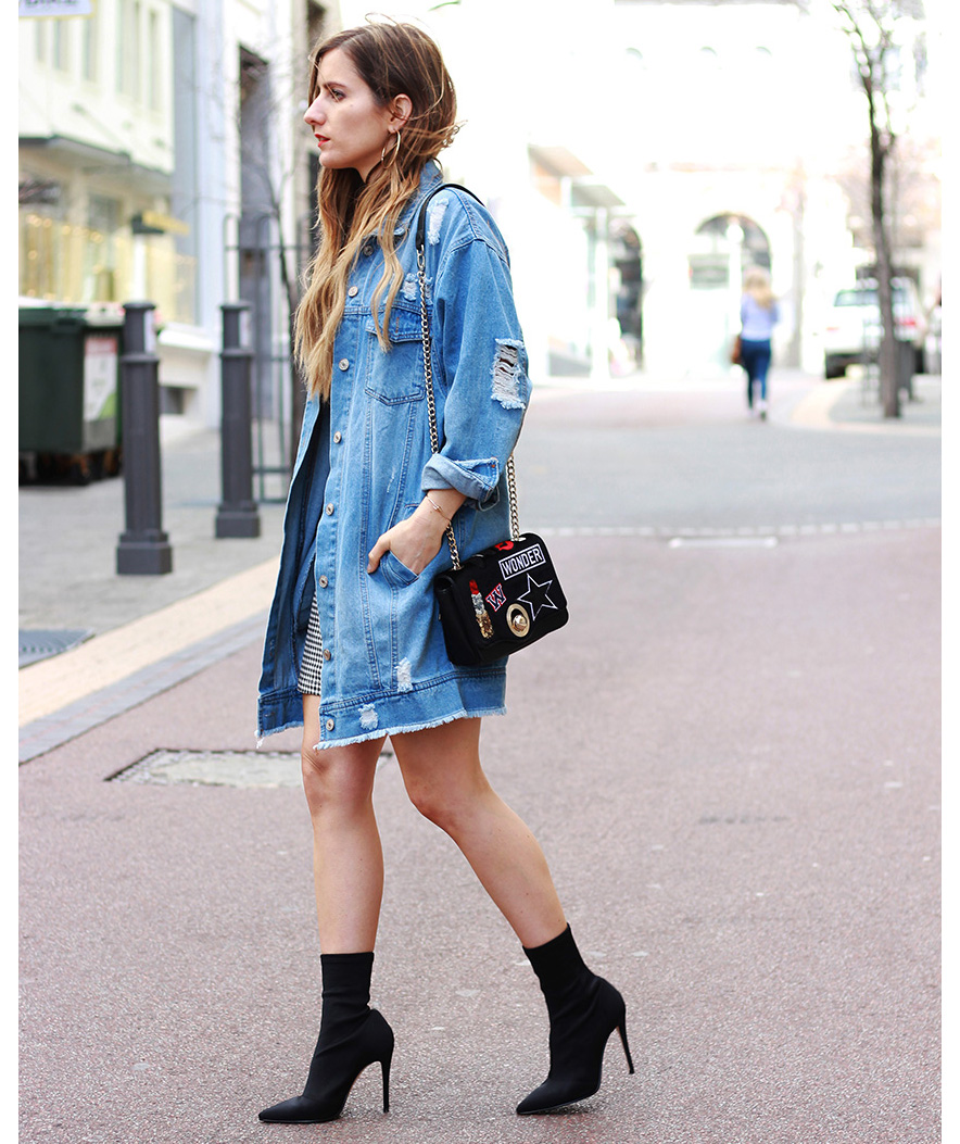 Woman wearing distressed oversized denim jacket with stiletto boots