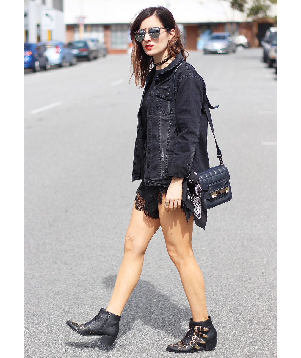 Woman wearing black denim jacket with edgy black accessories