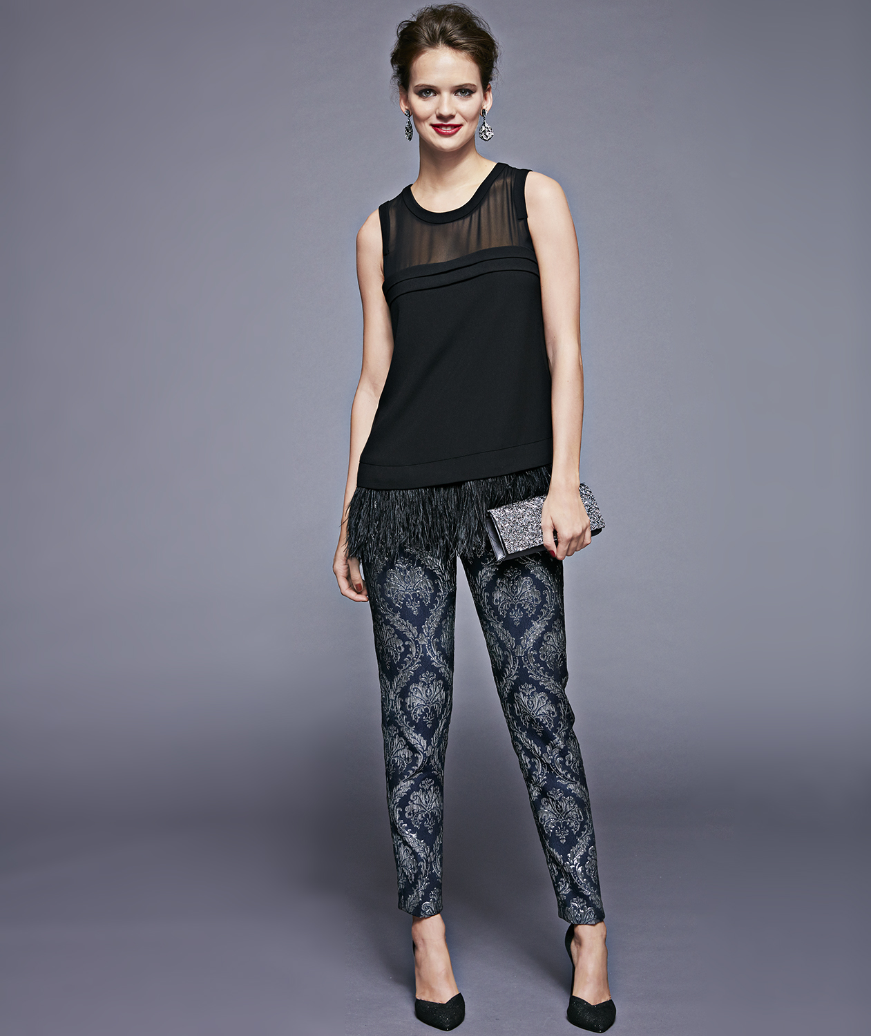 Model with black feather top and metallic patterned pants