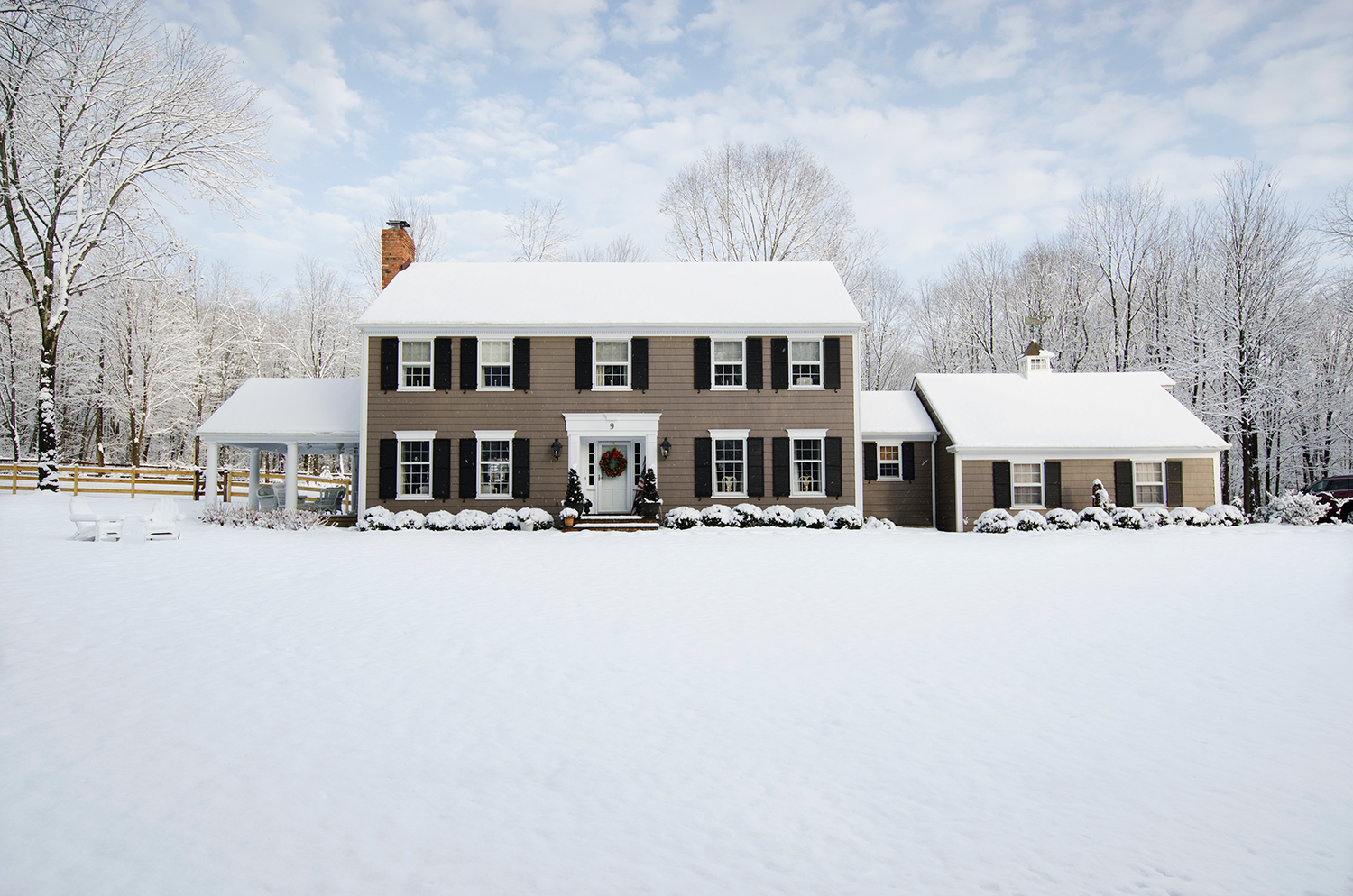 Colonial House Covered in Snow During Christmas