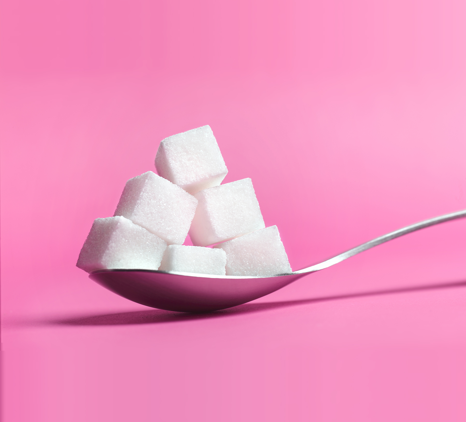Spoonful of sugar cubes on pink background