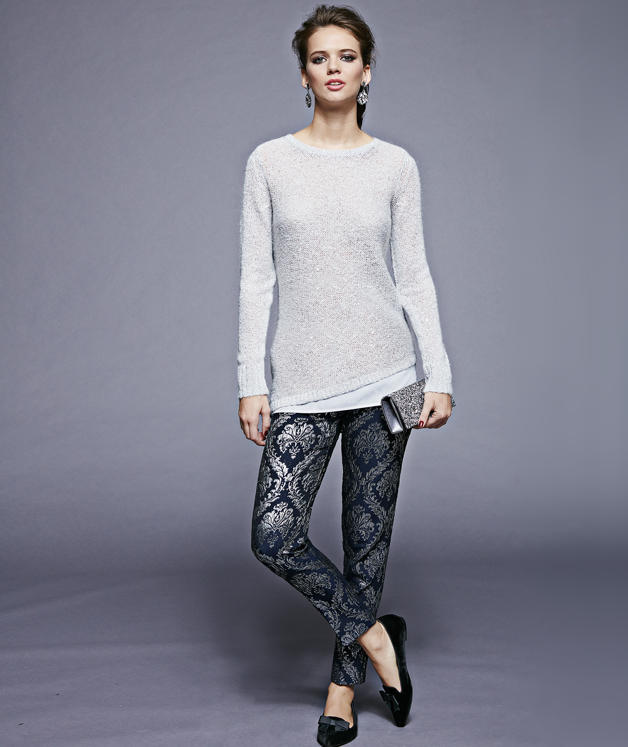 Model with gray sweater and metallic patterned pants