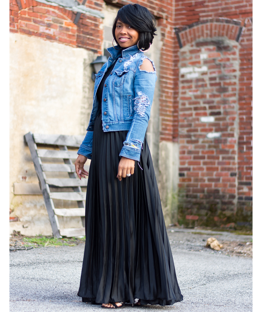 Woman wearing distressed jean jacket with pleated maxi skirt