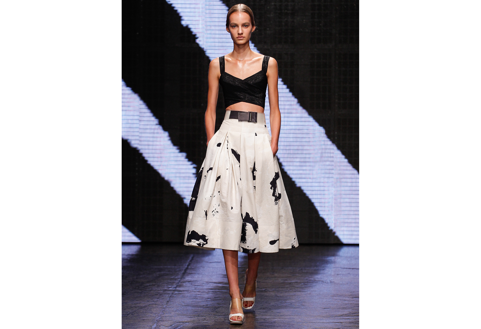 Model wearing cropped black top with full skirt