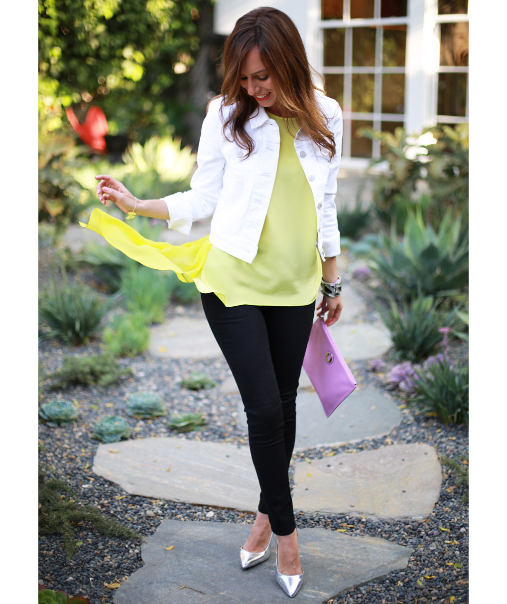 Woman wearing white denim jacket with yellow top and black jeans