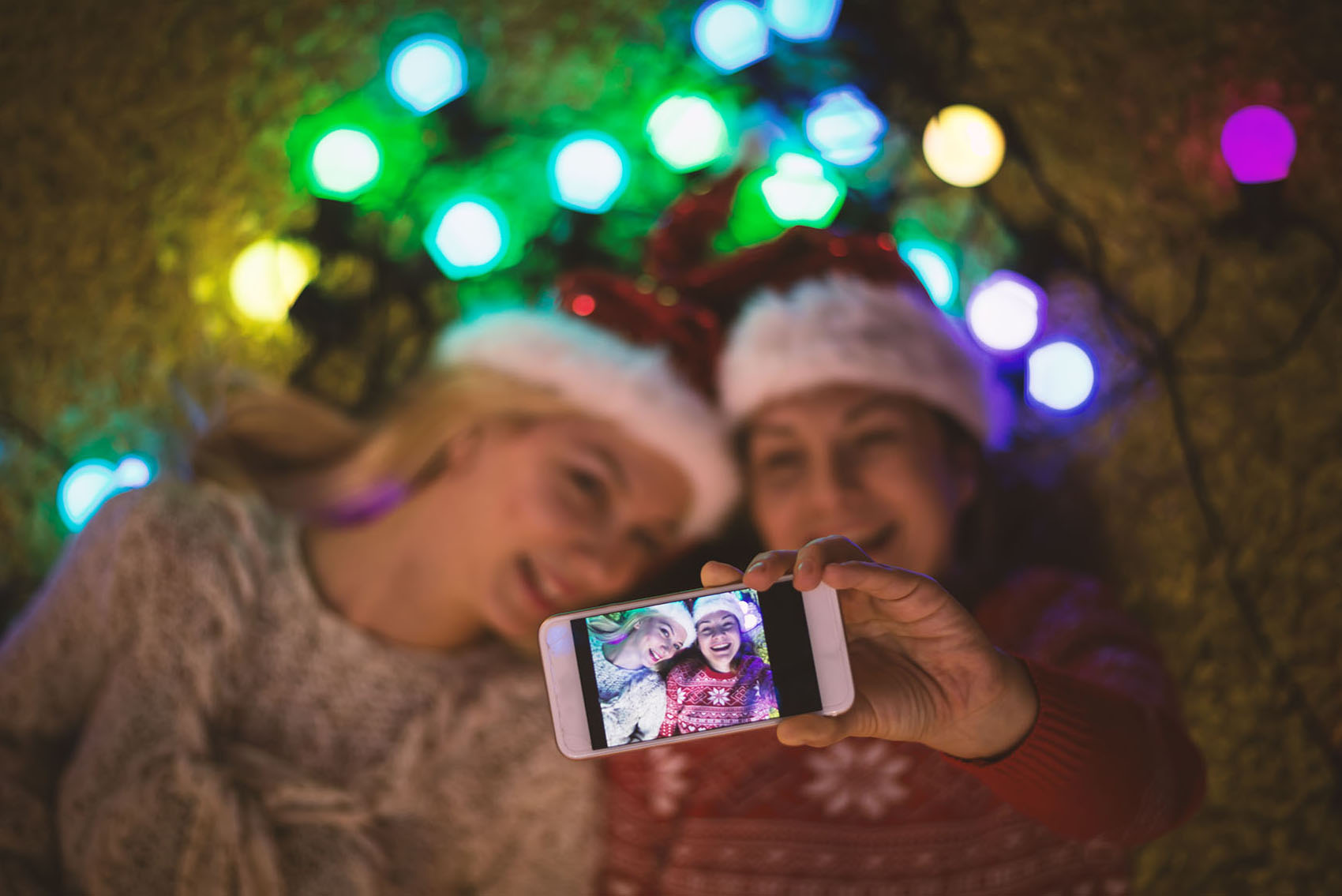 Two girls taking holiday selfie with smart phone against colored lights