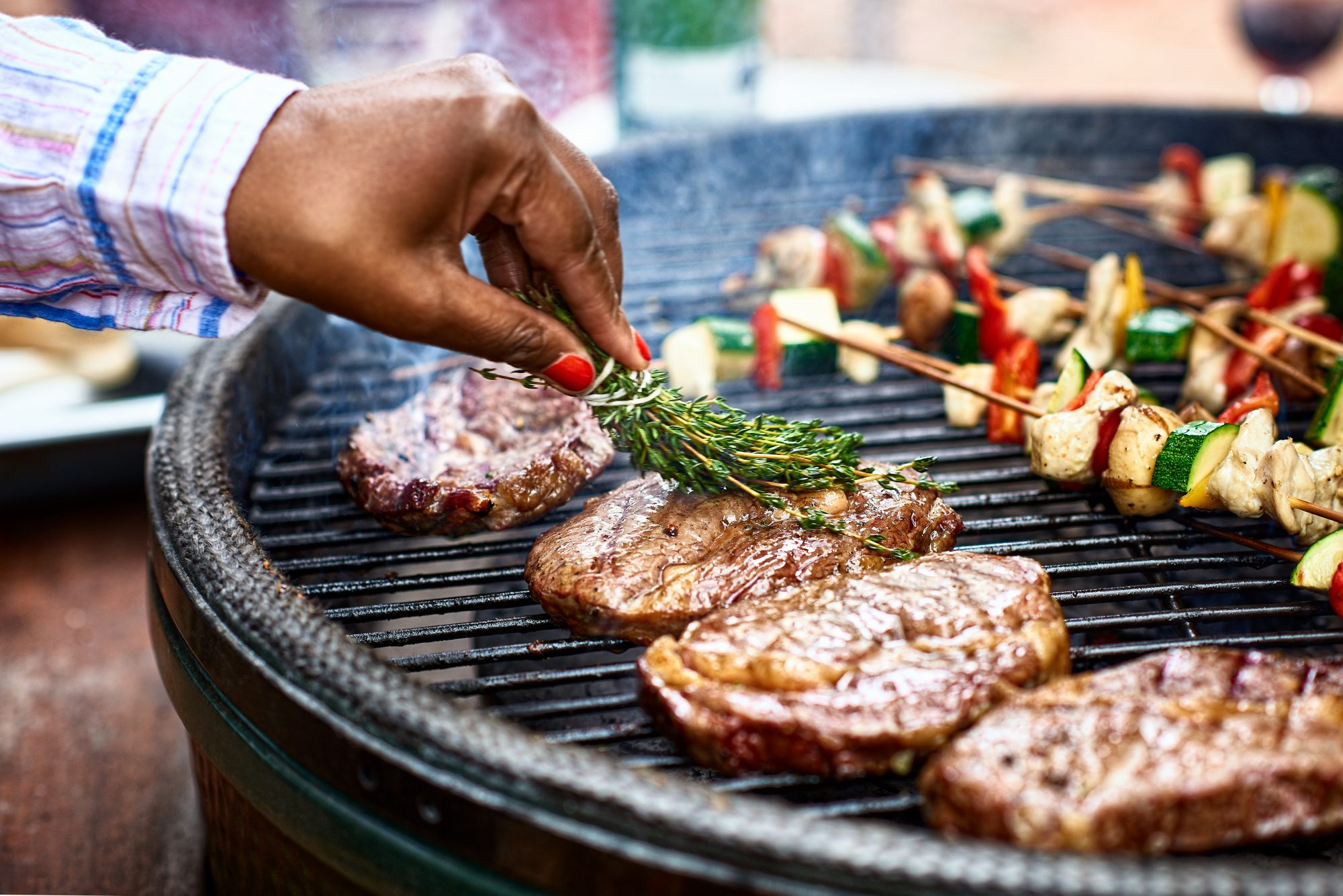 Steaks being seasoned with herbs as they cook on bbq grill: types of grills