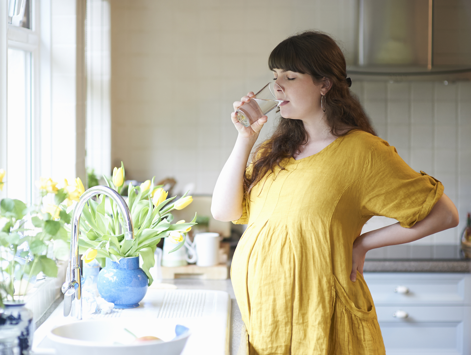 Pregnant woman drinking water in the kitchen