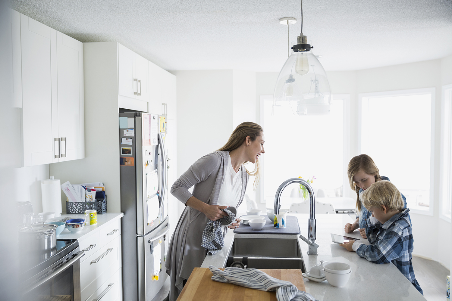 Woman Cleaning and Watching Her Kids