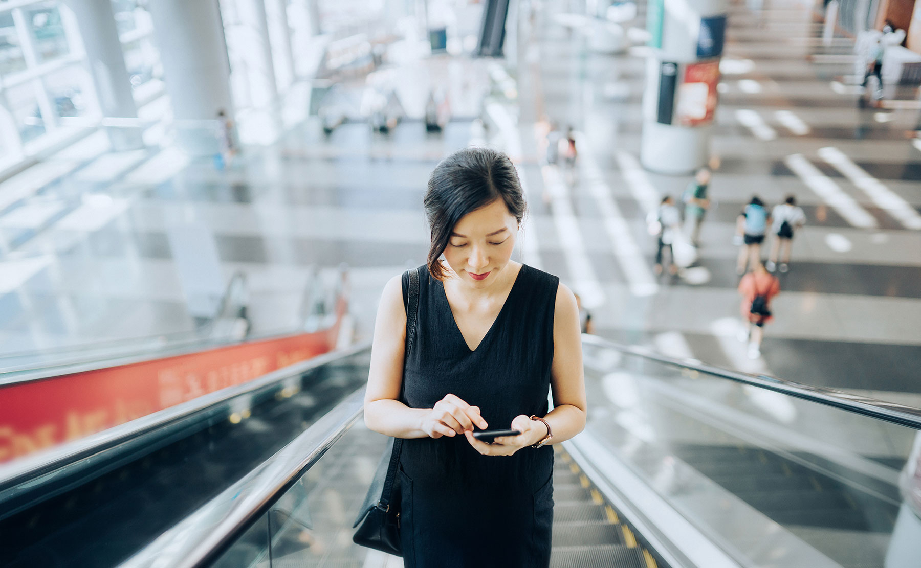 Woman using smartphone on escalator