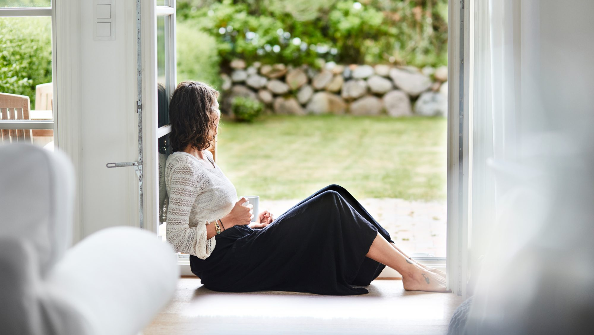 Woman sitting on the floor alone looking outside