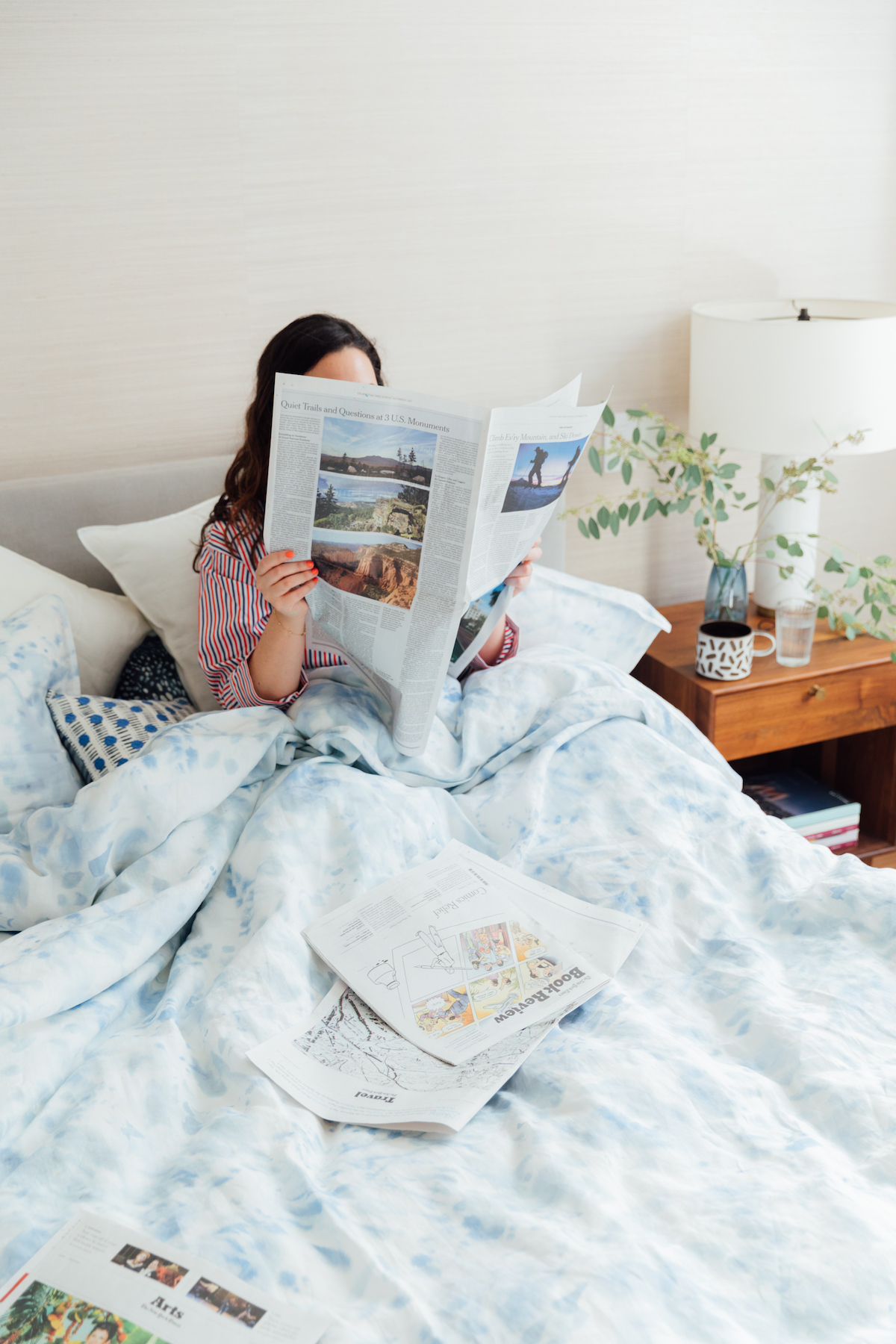 Rebecca Atwood reading newspaper in bed, with blue ocean duvet cover