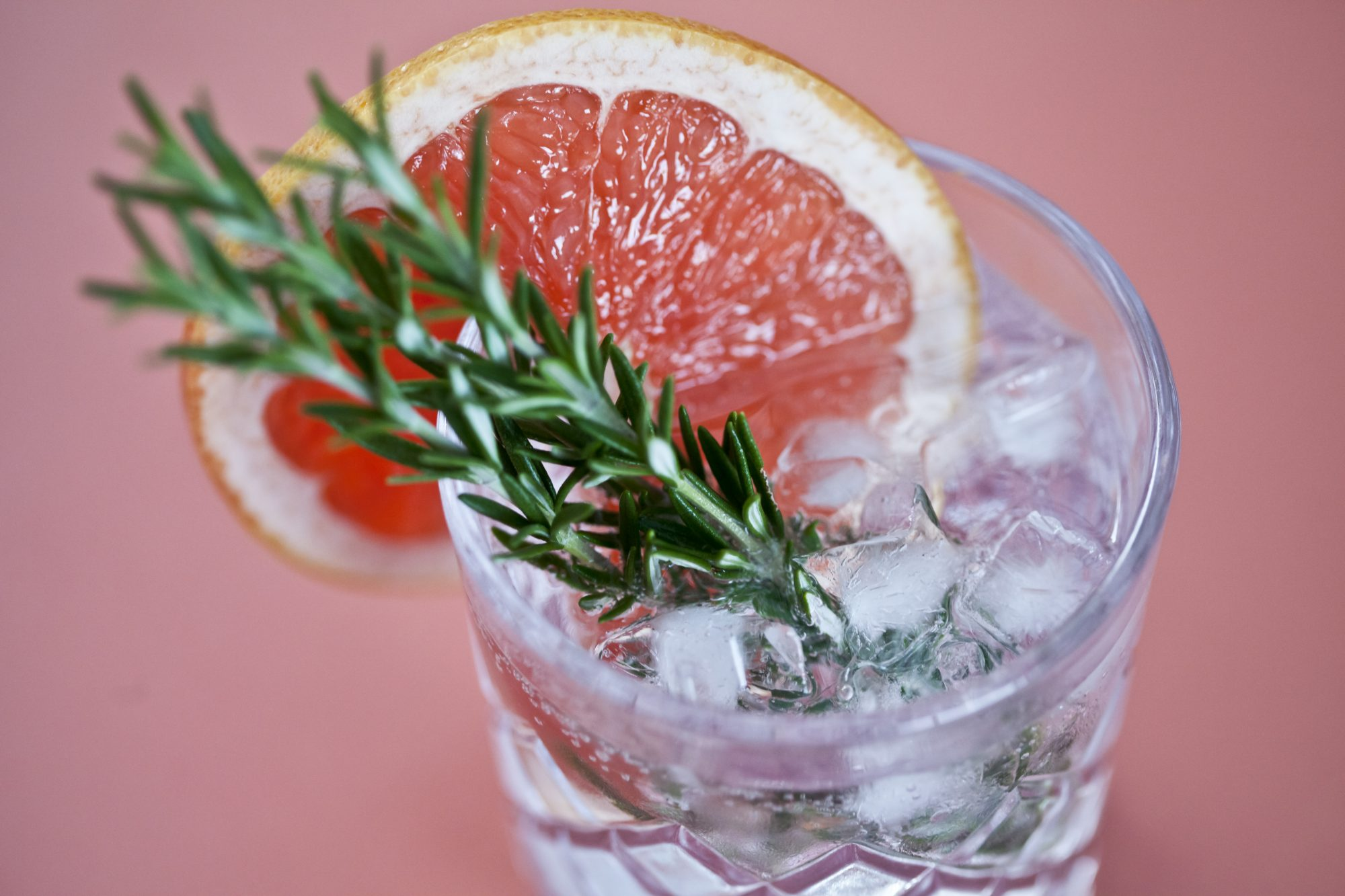 Gin and tonic with a slice of pink grapefruit and fresh herbs